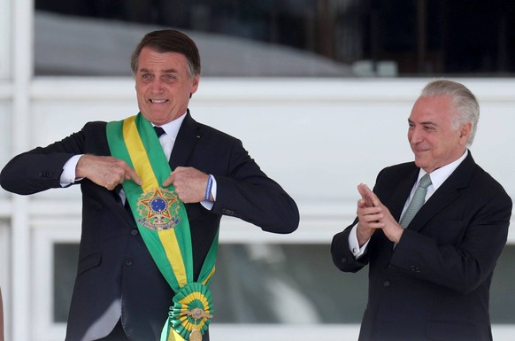 (190101) -- BRASILIA, Jan. 1, 2019 -- Photo provided by Agencia Estado shows Brazil s new President Jair Bolsonaro (L) pointing at the presidential sash after receiving it from outgoing President Michel Temer (R) in Brasilia, capital of Brazil, on Jan. 1, 2019. Army captain-turned-politician Jair Bolsonaro was sworn in as Brazil s president on Tuesday amid heightened security. AGENCIA ESTADO/Wilton Junior) ***BRAZIL OUT*** BRAZIL-BRASILIA-JAIR BOLSONARO-PRESIDENT-INAUGURATION AE PUBLICATIONxNOTxINxCHN