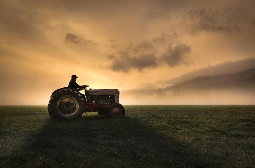 Farmer riding tractor during sunrise with vast open fields and bright orange sky on chilly, foggy morning.