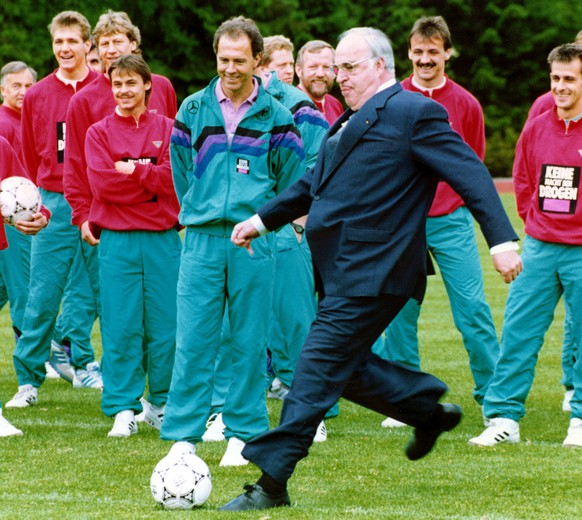 Italia world cup soccer preperations. German Chancellor Helmut Kohl (center right) kicking a ball during his visit to the trainings-camp of German national soccer team in Kamen near Dortmund while Team Coach Franz Beckenbauer (center) and some players (f.l.t.r.: Bodo Illgner, Guido Buchwald, Olaf Thon, Juergen Kohler, Pierre Littbarski) are looking on. The team prepares for the upcoming Soccer World Cup in Italy next month. (AP-Photo/Roberto Pfeil) 25.5.1990 |
