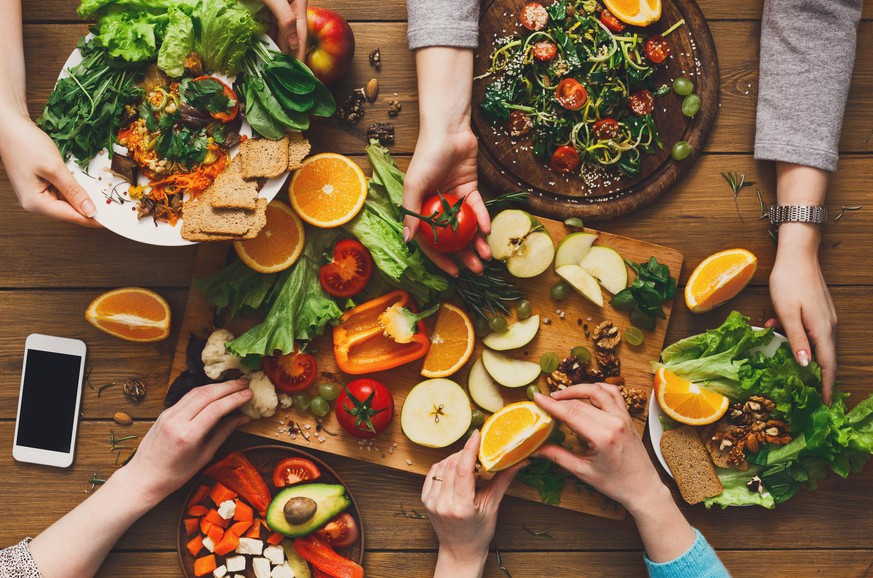 Eating healthy food, fruits and vegetables dinner table. Women at home together, top view, flat lay, crop