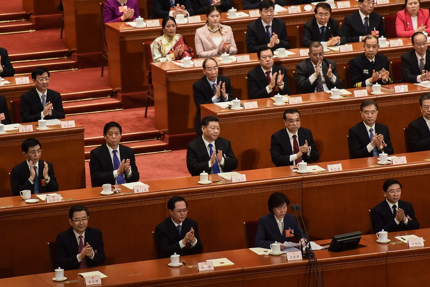 BEIJING, CHINA - MARCH 18:  (second raw) Chinese President Xi Jinping (C), Chinese Premier Li Keqiang (2-R) and Chairman of the National People's Congress Li Zhanshu (2-L) applaud with other members of the Party after the vote during the sixth plenary session of the National People's Congress (NPC) at the Great Hall of the People on March 18, 2018 in Beijing, China.  (Photo by Etienne Oliveau/Getty Images)