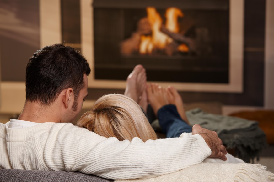 Young couple hugging on sofa in front of fireplace at home, rear view. Click here for more