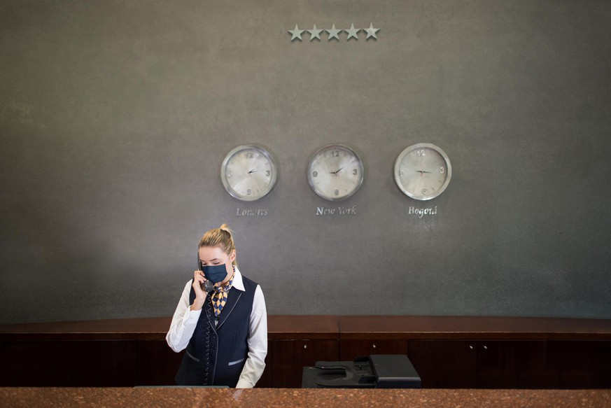 Latin American woman working at a hotel's reception wearing a facemask and talking on the phone - tourism industry