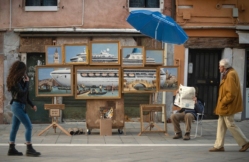 A street stall with oil paintings creating an image of a yacht in the Venice canal with a sign reading