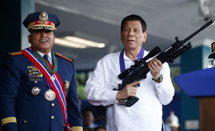 FILE - In this April 19, 2018 file photo, Philippine President Rodrigo Duterte, right, jokes to photographers as he holds an Israeli-made Galil rifle which was presented to him by former Philippine National Police Chief Director General Ronald
