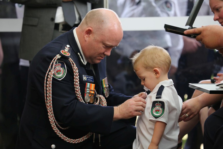 RFS Commissioner Shane Fitzsimmons presents a posthumous Commendation for Bravery and Service to the son of RFS volunteer Geoffrey Keaton at Keaton's funeral in Buxton, New South Wales, Australia January 2, 2020, in this picture obtained from social media. Mandatory credit NSW RURAL FIRE SERVICE/via REUTERS ATTENTION EDITORS - THIS IMAGE HAS BEEN SUPPLIED BY A THIRD PARTY. MANDATORY CREDIT. NO RESALES. NO ARCHIVES. TPX IMAGES OF THE DAY