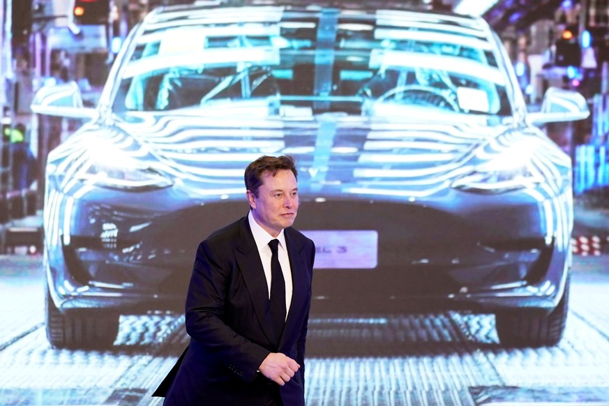 FILE PHOTO: Tesla Inc CEO Elon Musk walks next to a screen showing an image of Tesla Model 3 car during an opening ceremony for Tesla China-made Model Y program in Shanghai, China January 7, 2020. REUTERS/Aly Song/File Photo
