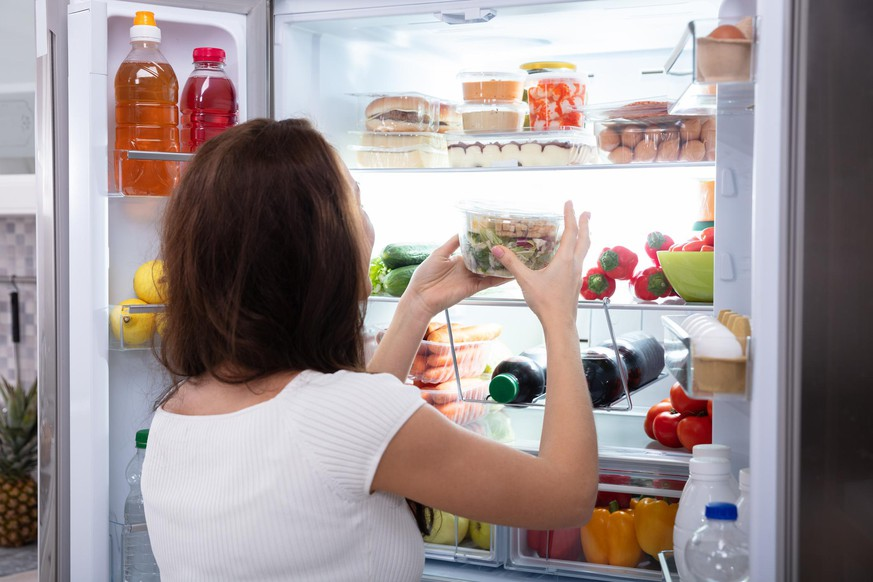 Rear View Of A Young Woman Taking Food From Refrigerator