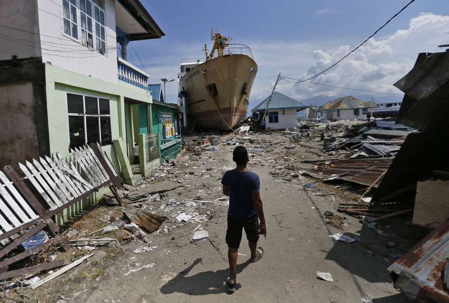 In this Thursday, Oct. 4, 2018, photo, a man walks past the Sabuk Nusantara 39 ship which was swept ashore by the tsunami in Wani village on the outskirt of Palu, Central Sulawesi, Indonesia Indonesia. A week after the magnitude 7.5 quake and tsunami hit central Sulawesi, the crew of the ferry remain on board, waiting for an assessment team to arrive and decide if the ship, its propeller jutting out over the waterfront, could be put back to sea. (AP Photo/Dita Alangkara)