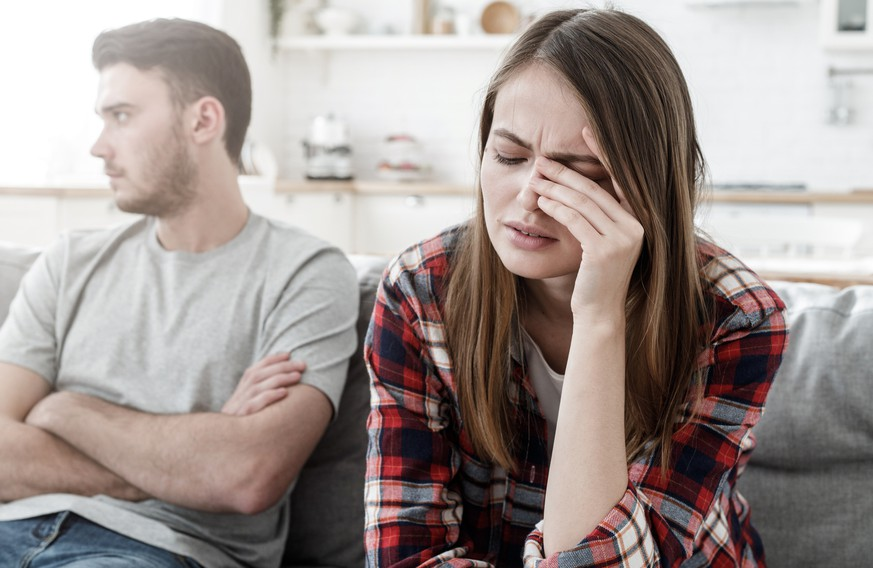 Couple conflict. Stressed crying female sitting on couch with abusive husband after quarrel, ready to divorce