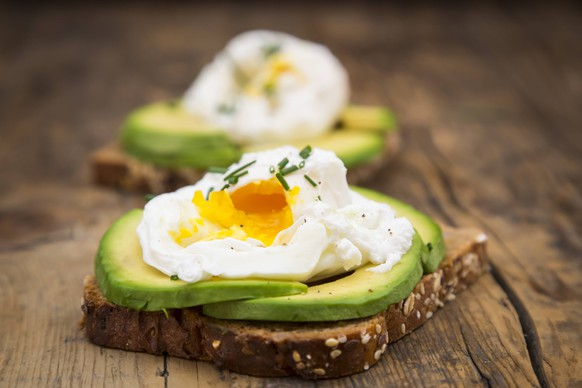 Wholemeal bread slices with sliced avocado and poached eggs on wood PUBLICATIONxINxGERxSUIxAUTxHUNxONLY LVF004673wholemeal BREAD slices With sliced Avocado and poached Eggs ON Wood PUBLICATIONxINxGERxSUIxAUTxHUNxONLY LVF004673