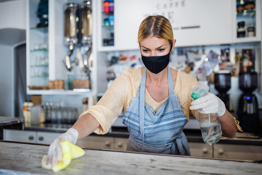 Coffee shop woman owner working with face mask and gloves, cleaning and disinfecting counter.
