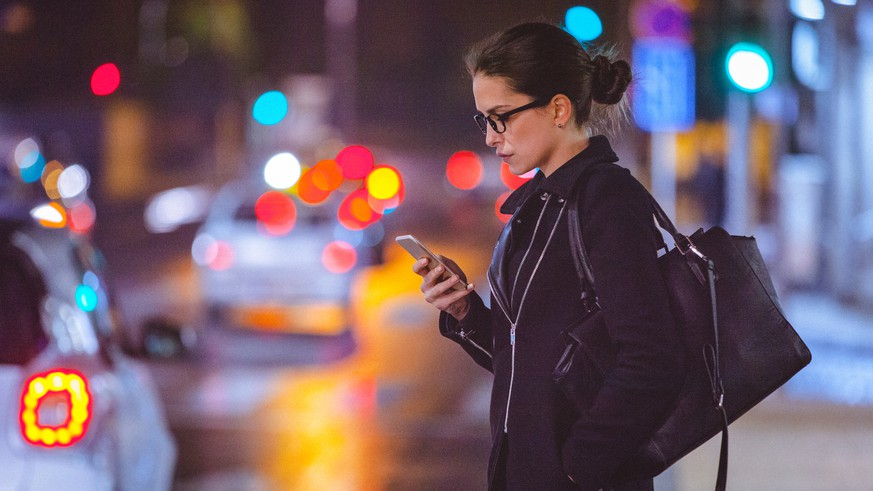 Close-up of a young woman using smart phone on the busy city street at night. The woman is serious while looking at the phone. She is dressed in black coat and wears a big black purse. Her long dark hair is swept back from the face and tied in a bun. It looks like she is waiting for a taxi or Uber. She seems tired and it could be that she is going home from a late work. The blurred colorful street and traffic lights are visible behind her. The shot is executed with available street light, and the copy space has been left.