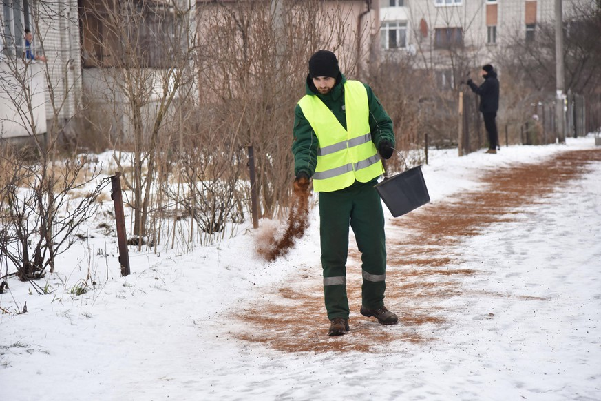 February 1, 2021, Lviv, Ukraine: Holding a bucket of coffee grounds, a municipal employee walks while scattering coffee grounds on a park path in Lviv..Lviv municipal services have started to use coffee grounds to fight ice in parks and squares. Lviv Ukraine - ZUMAs197 20210201_zaa_s197_075 Copyright: xPavloxPalamarchukx