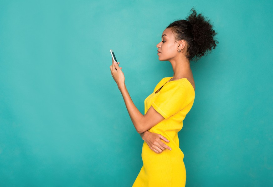 Young african-american woman typing message on smartphone on blue studio background, side view. Communication concept