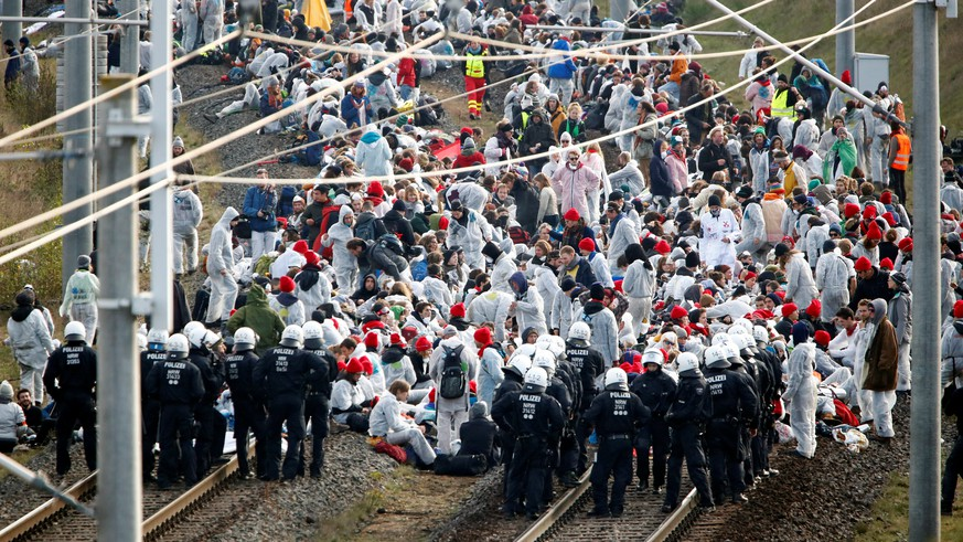 Environmental activists block a rail line as they protest for the preservation of the ancient forest