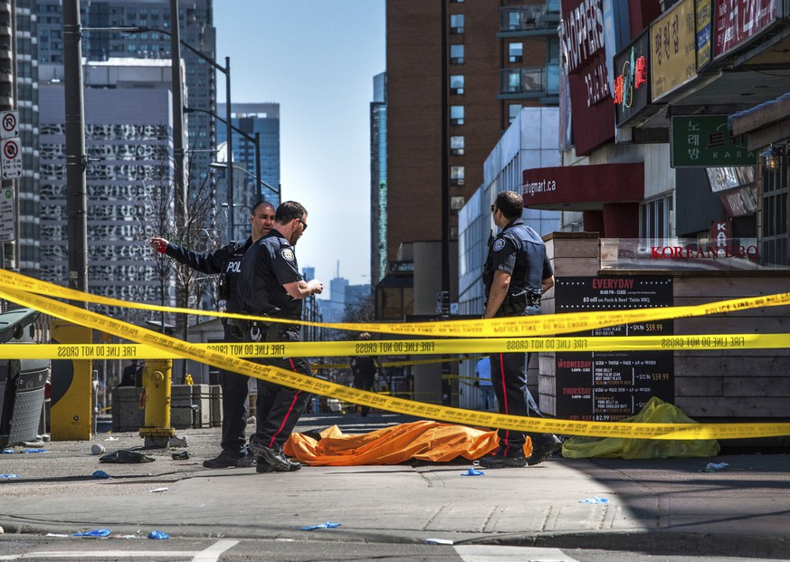 Police officers stand by a body covered on the sidewalk in Toronto after a van mounted a sidewalk crashing into a crowd  of pedestrians on Monday, April 23, 2018. The van apparently jumped a curb Monday in a busy intersection in Toronto and struck the pedestrians and fled the scene before it was found and the driver was taken into custody, Canadian police said. (Aaron Vincent Elkaim/The Canadian Press via AP)