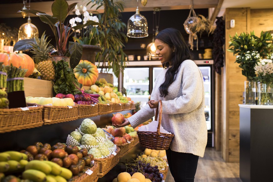 Young woman carrying wicker basket while buying fruits in grocery store model released Symbolfoto property released ABZF03176