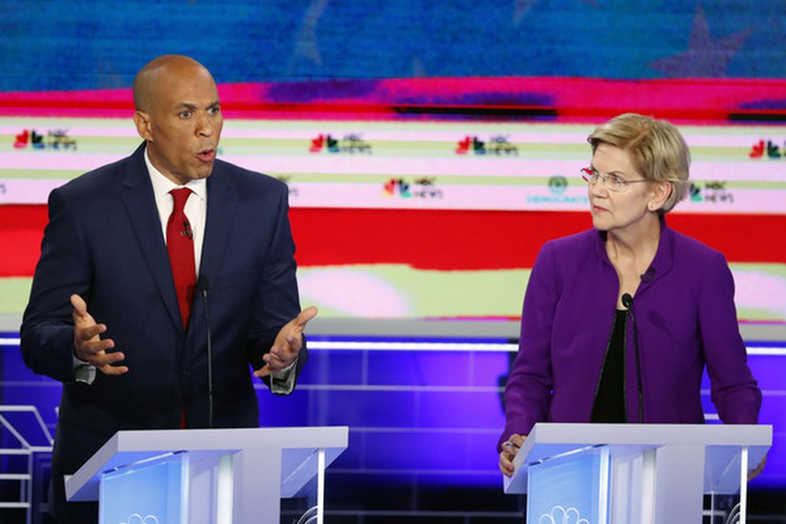 Democratic presidential candidate Sen. Cory Booker, D-N.J., speaks during a Democratic primary debate hosted by NBC News at the Adrienne Arsht Center for the Performing Art, Wednesday, June 26, 2019, in Miami, as Sen. Elizabeth Warren, D-Mass., listens. (AP Photo/Wilfredo Lee) |