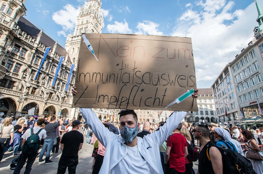 "May 9, 2020, Munich, Bavaria, Germany: Protest against an immunity passport, as well as compulsory vaccination. Despite ongoing relaxing measures, a ""Querfront"" (cross-front) mixture of 3,000 conspiracy theorists, QAnon followers, right-extremists, AfD figures, neonazis, hooligans, and Widerstand2020 assembled for a third weekend in Munich's city center, primarily at Marienplatz, to demonstrate for restoration of the Grundgesetz amid the Coronavirus crisis. Such demos and daily mini-demos with an overwhelming 2015-2016 Pegida quality are being staged throughout Germany, with two attacks on journalists for ARD and ZDF having taken place. Internally, members of the official Munich chat group have been planning attacks on journalists for the past week, with many of the more active members coming from right-extremist and neonazi circles and designating all journalists as ""antifa"". The posting of right-wing and Reichsbuerger memes is also commonplace, with acceptance from the administrator. (Credit Image: © Sachelle Babbar/ZUMA Wire 