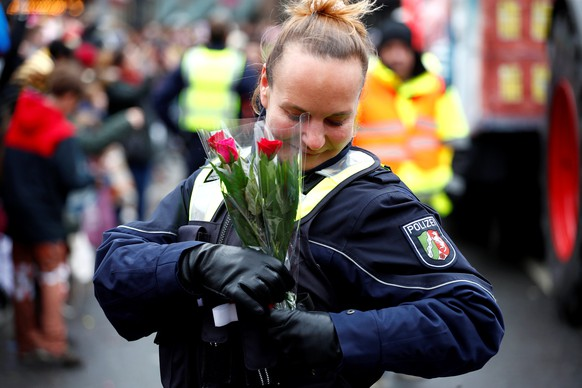 """A police officer places flowers in her uniform during the """"Rosenmontag"""" (Rose Monday) parade in Dusseldorf, Germany March 4, 2019. REUTERS/Wolfgang Rattay"""