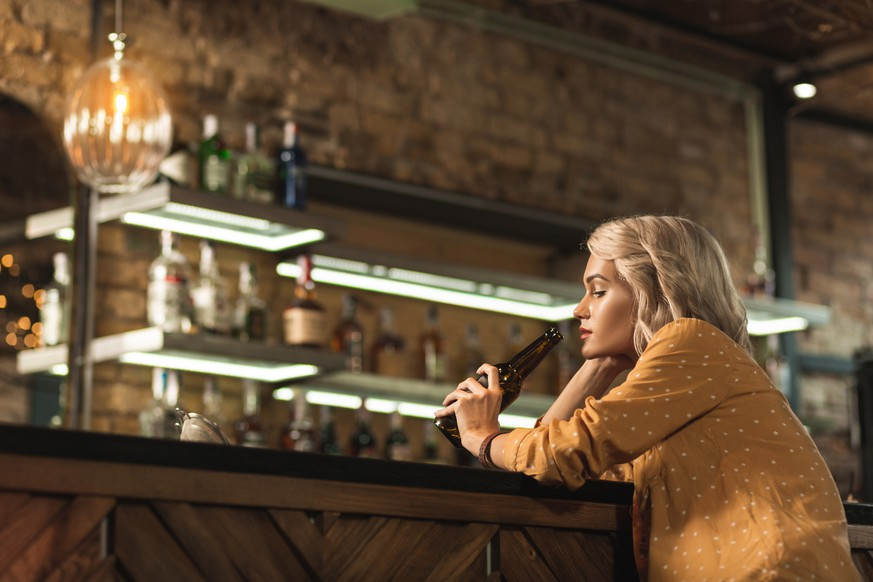 Bad day. Pretty blonde woman sitting at the bar counter and seeping beer while being upset with something