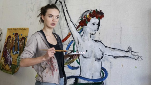 Oksana Shachko, activist of women's rights group Femen, speaks while painting a wall of her room in Kiev, Ukraine February 21, 2012. Picture taken February 21, 2012. REUTERS/Gleb Garanich
