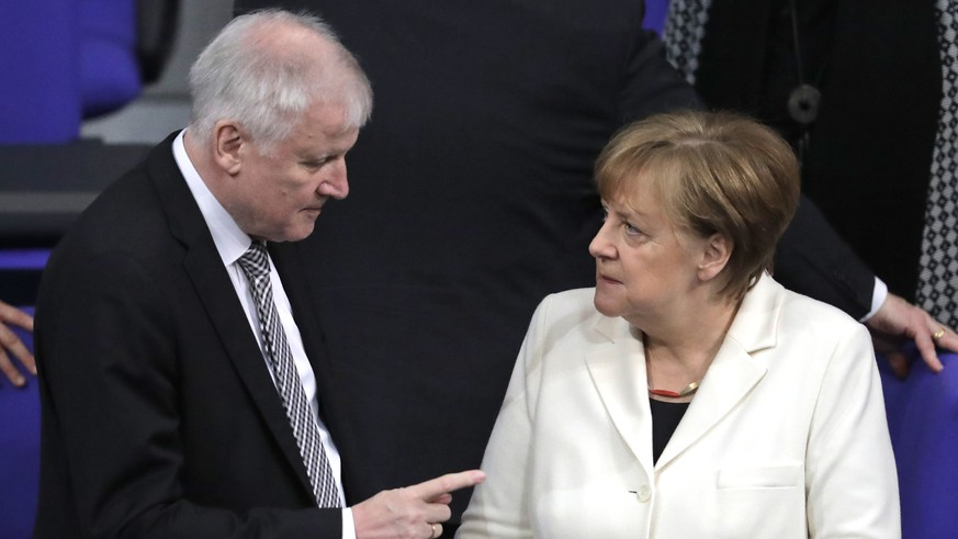 FILE - In this March 14, 2018 file photo German Interior Minister Horst Seehofer, left, talks to German Chancellor Angela Merkel  in the German parliament in Berlin. Germany's new interior minister is positioning himself to the right of Chancellor Angela Merkel on migration, telling a newspaper Islam is not a part of Germany Friday, March 16, 2018.  (AP Photo/Markus Schreiber,file)