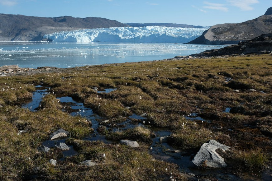 EQIP SERMIA, GREENLAND - AUGUST 01: Water from the Greenland ice sheet flows through heather and peat as the Eqip Sermia Glacier stands behind during unseasonably warm weather on August 01, 2019 at Eqip Sermia, Greenland. The nearby Eqip Sermia glacier is located approximately 350km north of the Arctic Circle, and while the calving of ice from its face is a natural process going back millions of years, the glacier's retreat of about 3 km over the last 100 years is a new phenomenon. (Photo by Sean Gallup/Getty Images)