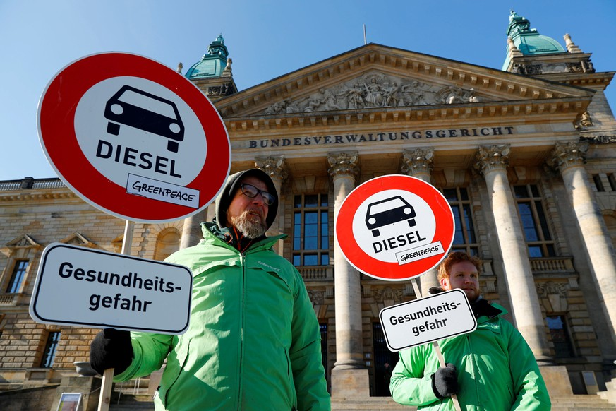 FILE PHOTO: Greenpeace environmental activists protest in front of Germany's Federal Administrative Court before it decides whether German law provides a legal basis for cities to ban diesel cars to help reduce air pollution, in Leipzig, Germany February 27, 2018. The placards read: