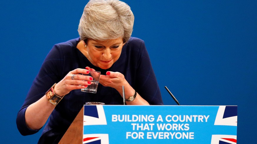 FILE PHOTO: Britain's Prime Minister Theresa May struggles with her glass of water after suffering a coughing fit whilst addressing the Conservative Party conference in Manchester, October 4, 2017. To match Special Report BRITAIN-EU/MAY     REUTERS/Phil Noble/File Photo