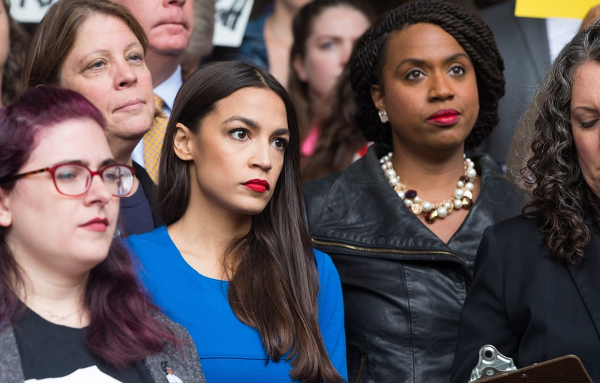 BOSTON, MA - OCTOBER 01:  New York Democratic congressional candidate Alexandria Ocasio-Cortez (in blue) stands with Boston City Councilor and Democratic congressional candidate Ayanna Pressley (R) at a rally calling on Sen. Jeff Flake (R-AZ) to reject Judge Brett Kavanaugh's nomination to the Supreme Court on October 1, 2018 in Boston, Massachusetts. Sen. Flake is scheduled to give a talk at the Forbes 30 under 30 event in Boston after recently calling for a one week pause in the confirmation process to give the FBI more time to investigate sexual assault allegations.  (Photo by Scott Eisen/Getty Images)