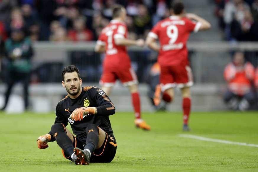 Dortmund goalkeeper Roman Buerki sits on the ground after Bayern's Robert Lewandowski scored his side's opening goal during the German Bundesliga soccer match between FC Bayern Munich and Borussia Dortmund in Munich, Germany, Saturday, March 31, 2018. (AP Photo/Matthias Schrader)