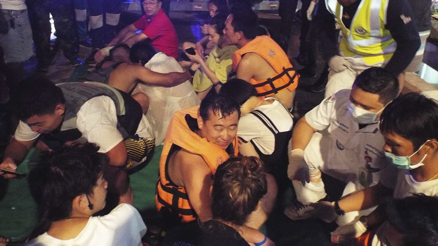 Rescued tourists from a boat that sank gather on a pier Thursday, July 5, 2018, on the island of Phuket, southern Thailand. A boat carrying dozens of Chinese tourists overturned in rough seas off southern Thailand and dozens of passengers were unaccounted for, the Phuket governor said.