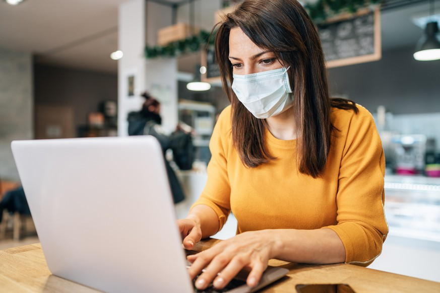 Portrait of young woman using laptop at cafe wearing  face protective mask to prevent infectious diseases