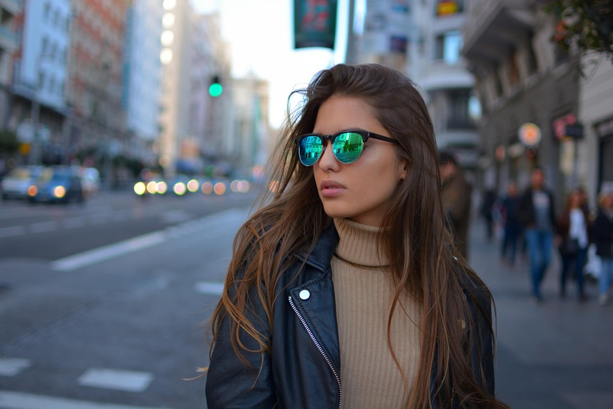 urban young girl walking on the Gran Via street in Madrid during sunset wearing sunglasses and black jacket