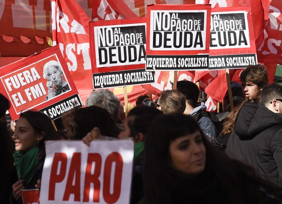 Political parties opponents and social movements protesters hold signs that read in Spanish: