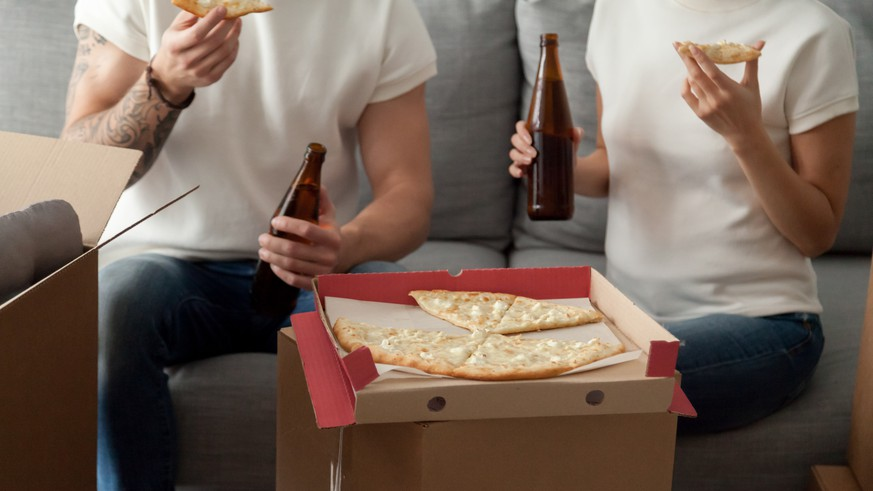 Couple eating pizza celebrating housewarming party on moving day, man and woman enjoying beer and snack sitting on sofa with unpacked boxes around, move in new home, delivery service, close up view, Pizza, Umzug