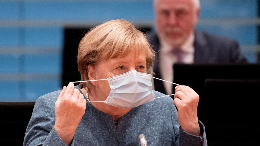 German Chancellor Angela Merkel removes her face mask before the National Integration Prize honoring engagement for integration in Berlin, October 5, 2020.  Kay Nietfeld/Pool via REUTERS