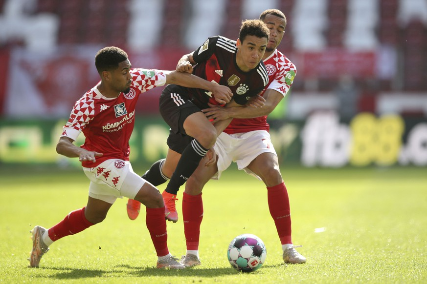 Mainz's Phillipp Mwene, left, Bayern's Jamal Musiala and Mainz's Robin Quaison challenge for the ball during the German Bundesliga soccer match between FSV Mainz and FC Bayern Munich in Mainz, Germany, Saturday, April 24, 2021. (AP Photo/dpa via AP)