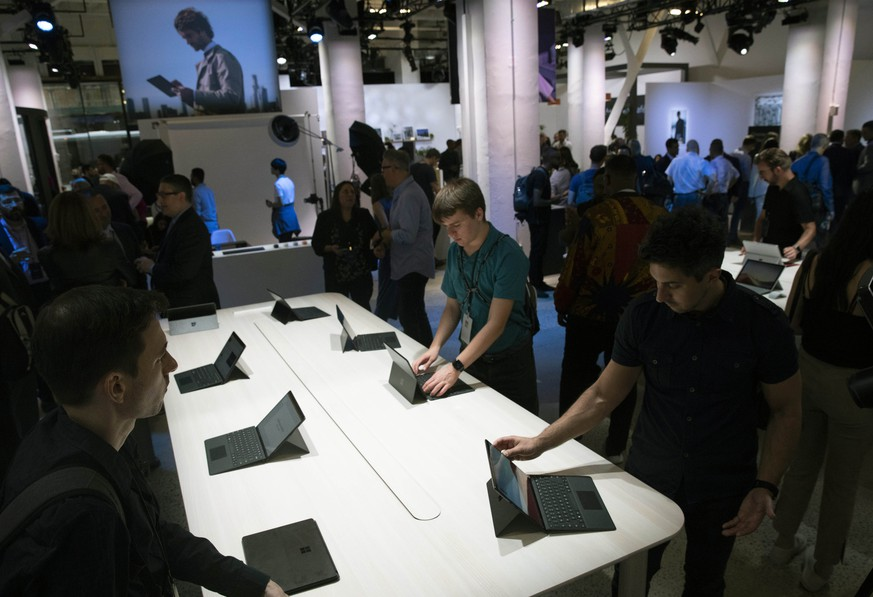 People try the Microsoft Surface Pro X, Wednesday, Oct. 2, 2019, in New York. (AP Photo/Mark Lennihan) |