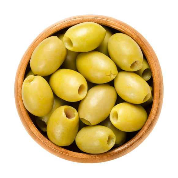 Pitted and marinated green olives in wooden bowl. Fruits of the European olive, Olea europaea. Unripe table olives with yellow to green color. Isolated macro food photo close up from above over white.