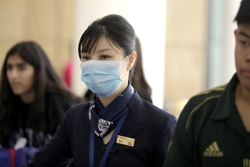 A flight crew member from China Eastern Airlines leaves the airport wearing a face mask after arriving in Sydney Thursday, Jan. 23, 2020, on a flight from Wuhan, China. China closed off a city of more than 11 million people as part of a radical effort to prevent the spread of a deadly virus that has sickened more than 500 people and has begun to spread to other cities and countries in the region. (AP Photo/Rick Rycroft)