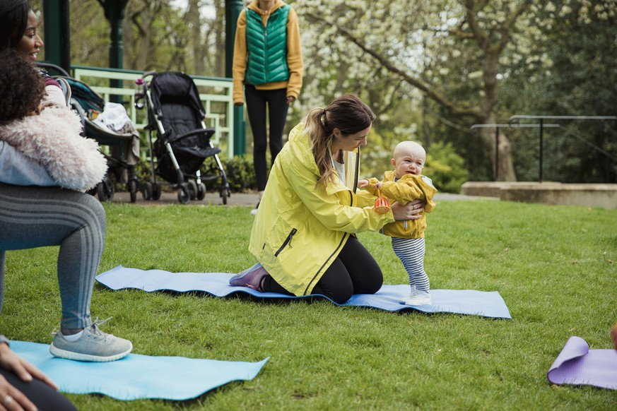 A mother is attending an exercise class in the park whereby her and her cute son are doing yoga.