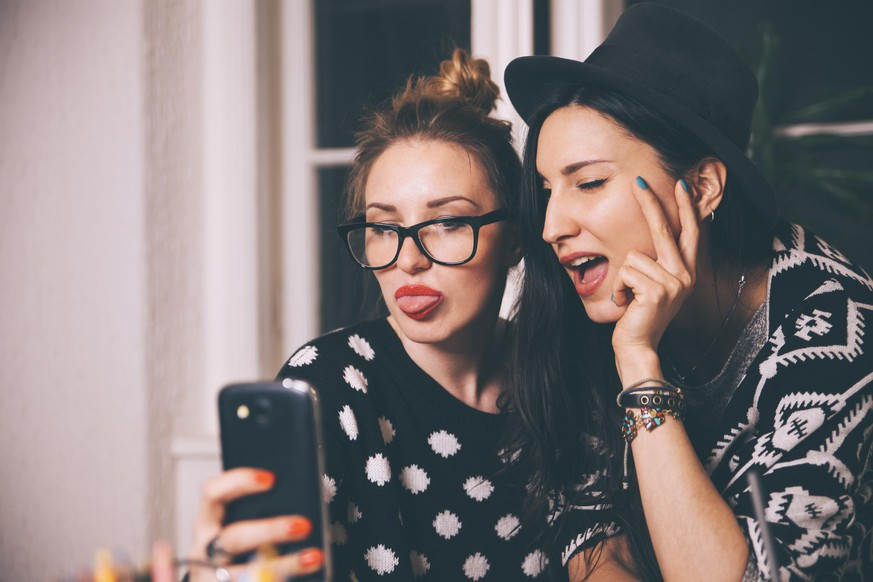 Vintage toned portrait of two fashionable young women taking a selfie photograph with a smartphone, sticking tongue out.