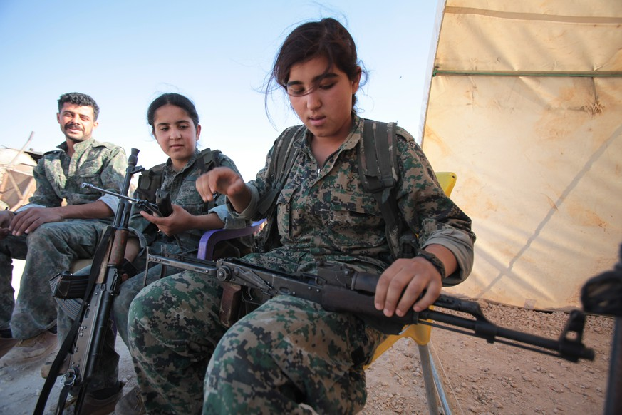 KOBANE, SYRIA - JUNE 20: (TURKEY OUT) A Kurdish People's Protection Units, or YPG's woman fighter controls her AK-47 in a camp at the outskirts of the destroyed Syrian town of Kobane, also known as Ain al-Arab, Syria. June 20, 2015. Kurdish fighters with the YPG took full control of Kobane and strategic city of Tal Abyad, dealing a major blow to the Islamic State group's ability to wage war in Syria. Mopping up operations have started to make the town safe for the return of residents from Turkey, after more than a year of Islamic State militants holding control of the town. (Photo by Ahmet Sik/Getty Images)