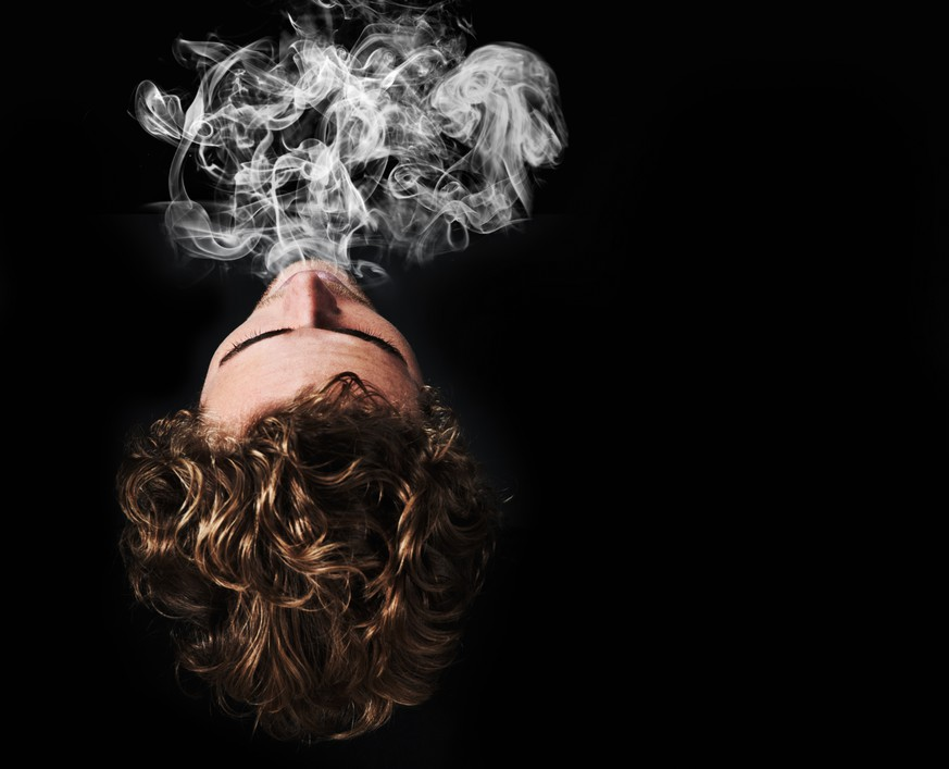 Top view a young man blowing out smoke against a black background