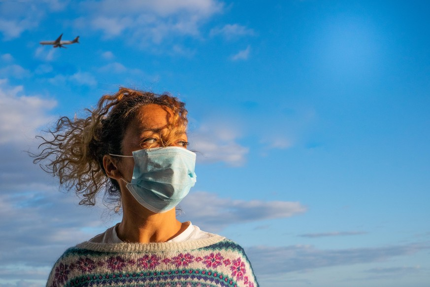 one curly and beautiful woman wearing medical mask to prevent any type of disease or virus like coronavirus or covid-19 - airplane inside of her head at the background like risky vacations hazard