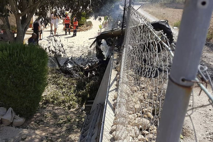 This photo provided by Incendios f.Baleares shows wreckage by a fence near Inca in Palma de Mallorca, Spain, Sunday Aug. 25, 2019. Authorities in Mallorca say at least 5 people have died in a collision between a helicopter and a light plane on the Spanish island. (Incendios f.Baleares Via AP)