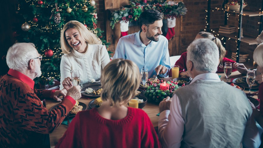 Photo of full family gathering sitting dinner table communicating chatting overjoyed x-mas party multi-generation in newyear decorated living room indoors
